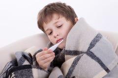 El muchacho enfermo con un termómetro Imagen de archivo libre de regalías