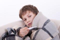 El muchacho enfermo con un termómetro Fotografía de archivo libre de regalías