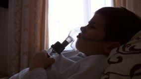 El muchacho enfermo del niño en máscara respira a través del compresor de los inhaladores con la medicación para la prevención de almacen de metraje de vídeo