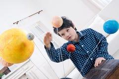 El muchacho enfocado que mira los planetas modela en casa Imagen de archivo libre de regalías