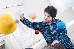 El muchacho enfocado que mira los planetas modela en casa Foto de archivo libre de regalías
