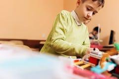 El muchacho enfocado vestido en suéter verde se sienta en la tabla en la escuela de la robótica y hace un robot del robótico fotos de archivo