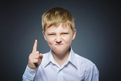 El muchacho enojado descontentado con amenaza al finger aislado en fondo gris Fotografía de archivo