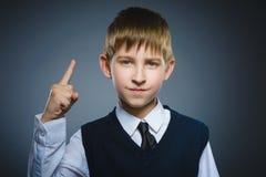 El muchacho enojado descontentado con amenaza al finger aislado en fondo gris Foto de archivo
