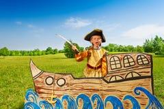El muchacho enojado en traje del pirata grita y sostiene la espada Imagen de archivo libre de regalías