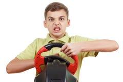 El muchacho enojado juega una videoconsola de conducción, aislada en blanco foto de archivo libre de regalías