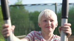 El muchacho entra para los deportes en un instructor elíptico en el parque en verano almacen de video