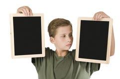 El muchacho entre dos tableros negros endereza Foto de archivo