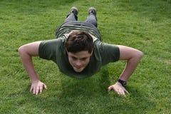 El muchacho entrena a pectorales afuera en el jardín Imagenes de archivo