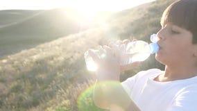 El muchacho es agua potable de la botella plástica en los rayos de Sun de la puesta del sol pasa a través almacen de metraje de vídeo