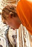 El muchacho es agua potable en un público Fotografía de archivo