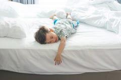 El muchacho es de salto y que juega por la mañana en la cama imágenes de archivo libres de regalías
