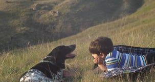 El muchacho es mentiras en la alfombra en la hierba en la tarde y la mirada en su perro almacen de video