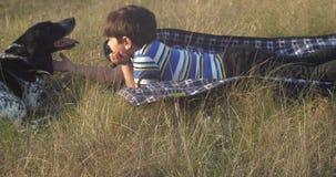 El muchacho es mentiras en la alfombra en la hierba en la tarde y el vientre del rasguño de su perro metrajes