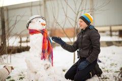 El muchacho es muñeco de nieve moldeado en la yarda en el invierno Fotografía de archivo