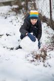 El muchacho es muñeco de nieve moldeado en la yarda en el invierno Fotos de archivo