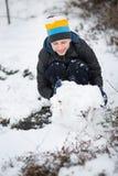 El muchacho es muñeco de nieve moldeado en la yarda en el invierno Foto de archivo libre de regalías