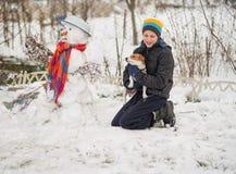 El muchacho es muñeco de nieve moldeado en la yarda en el invierno Fotografía de archivo libre de regalías