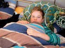 El muchacho es restingin la cama Foto de archivo