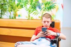 El muchacho es serio con un smartphone y el reloj elegante se está sentando en el banco y está mirando en el teléfono Imagen de archivo libre de regalías
