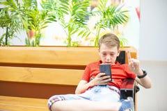 El muchacho es serio con un smartphone y el reloj elegante se está sentando en el banco y está mirando en el teléfono Foto de archivo