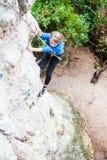 El muchacho es un escalador de roca Fotografía de archivo