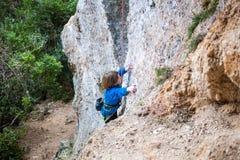 El muchacho es un escalador de roca Fotografía de archivo libre de regalías