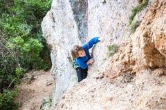 El muchacho es un escalador de roca Imagen de archivo