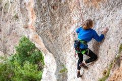 El muchacho es un escalador de roca Foto de archivo