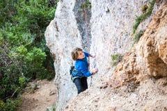 El muchacho es un escalador de roca Imagenes de archivo