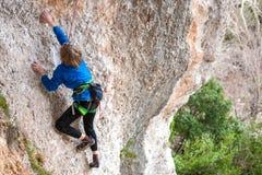 El muchacho es un escalador de roca Foto de archivo libre de regalías