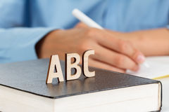El muchacho escribe en un cuaderno de la escuela, letras de madera ABC en el libro Imágenes de archivo libres de regalías