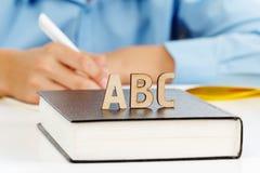 El muchacho escribe en un cuaderno de la escuela, letras de madera ABC en el libro Imagenes de archivo