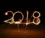 El muchacho escribe a 2018 la chispa del fuego artificial de la Feliz Año Nuevo Foto de archivo