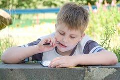 El muchacho escribe a los escritura-libros imagen de archivo