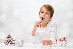 El muchacho escribe una letra a Santa Claus Imagen de archivo libre de regalías