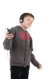 El muchacho escucha la música Foto de archivo