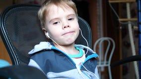 El muchacho escucha la música a través de los auriculares En el cuarto de niños el niño disfruta de música almacen de metraje de vídeo