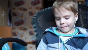 El muchacho escucha la música a través de los auriculares En el cuarto de niños el niño disfruta de música almacen de video