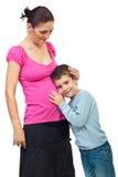 El muchacho escucha su panza embarazada de la madre Fotografía de archivo libre de regalías