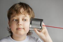 El muchacho escucha teléfono de la poder de estaño Fotografía de archivo libre de regalías