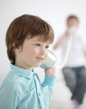 El muchacho escucha teléfono de la lata Imagenes de archivo