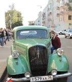 El muchacho escudriña la cabina del coche retro Foto de archivo