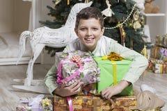 El muchacho está abrazando los regalos de la Navidad Foto de archivo