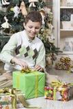 El muchacho está abriendo los regalos de la Navidad Fotografía de archivo libre de regalías