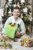 El muchacho está abriendo los regalos de la Navidad Imágenes de archivo libres de regalías