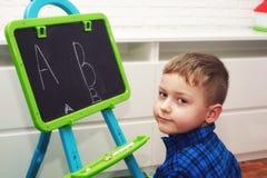 El muchacho está aprendiendo leer y escribir El niño aprende el alfabeto imagenes de archivo