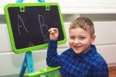 El muchacho está aprendiendo leer y escribir El niño aprende el alfabeto fotos de archivo