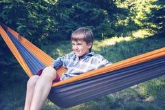 El muchacho está balanceando en una hamaca, con la cara divertida Imagen de archivo libre de regalías