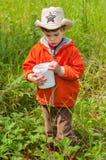 El muchacho está buscando bayas en el prado Imagen de archivo libre de regalías
